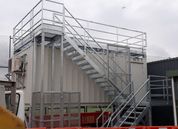Plane flying over container with stairs