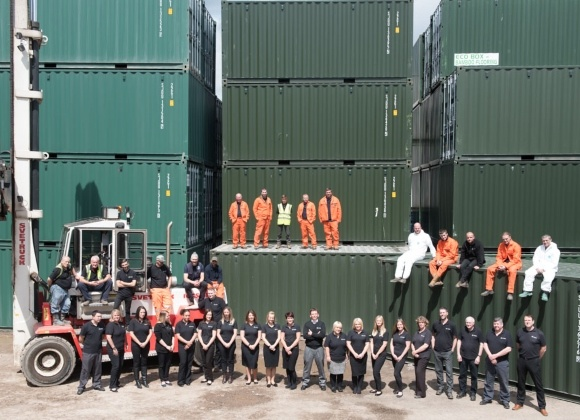 Staff on fork lift and green containers