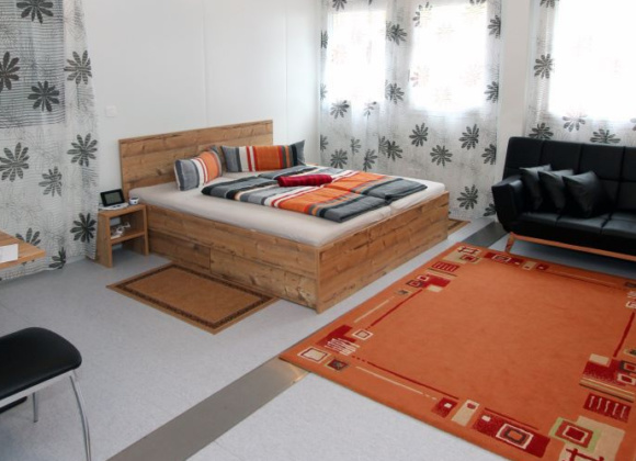Bedroom with orange carpet and black sofa