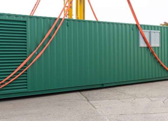 Green container being lifted by orange straps