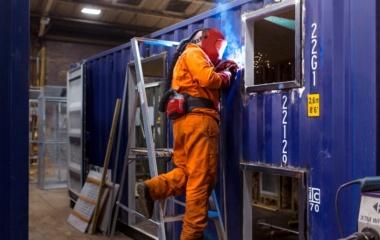 Welder working on container window