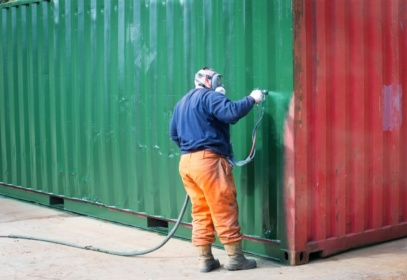 Spray painting red container green